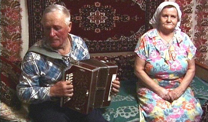 Гармонных дел мастер Анатолий Золотов играет на кирилловской гармони в присутствии жены
