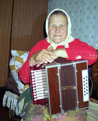 Пожилая женщина с кирилловской гармонью в руках